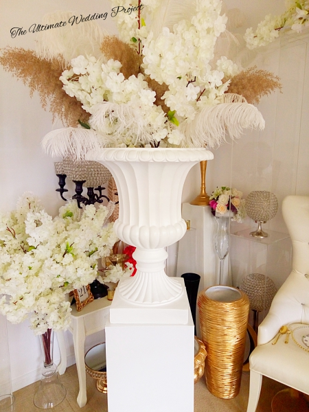 White Planter on white pedestals with florals.